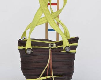 Bag shaped box of chocolate and green straps.