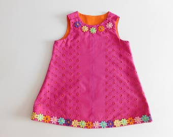 Cerise broderie anglais pinafore with orange lining and multi-col flower trim.