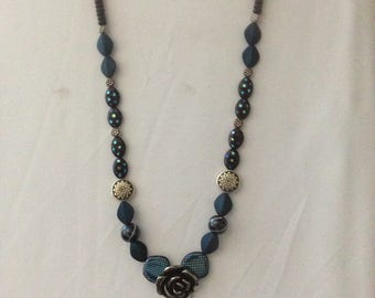 Royal blue necklace featuring a silver and black rose