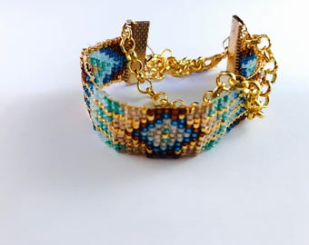 Handemade Miyuki bracelet from By Adinda in gold, blue, light blue, green and brown with golden chain