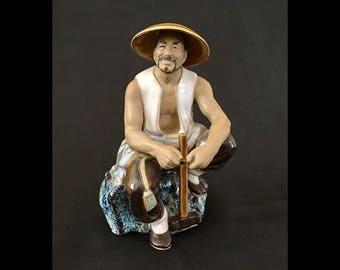 Chinese Mud Man (Mudman) Sitting on a Rock | China