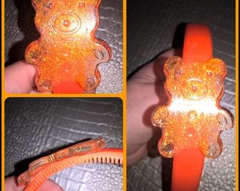 large orange headband decorated with a bear