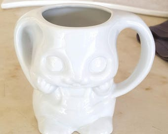 Mug in the shape of rabbit with kids in white porcelain handle