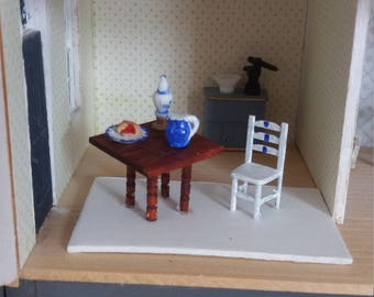 A one 1/4 inch scale tiny table with a hand painted chair.There is an oil lamp , Cherry pie and a blue and white jug of cream,on the table.