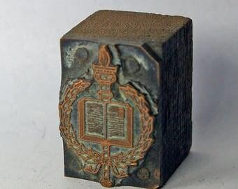 Vintage letterpress printing block: Laurel, torch, and book