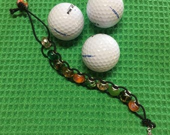 Golf beaded stroke counter in green/orange with a fleur de lis charm and clasp to attach to your belt hoop or golf bag
