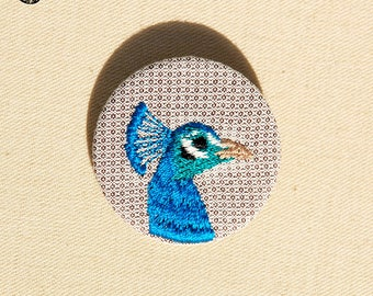 Small embroidered head of the majestic Peacock brooch