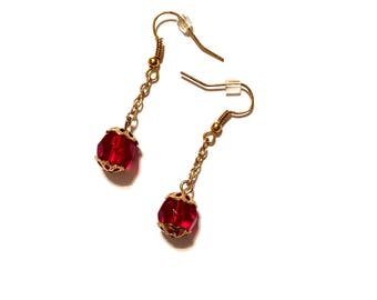 Red Glass Earrings. Dangle 1.75 inches long. Gold plated chain and ear wires.