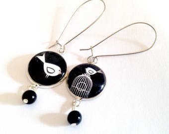 Drop earring, cabochon bird and cage, black and white, silver, black beads.