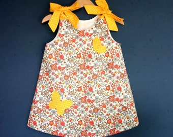 Floral baby dress with butterfly, yellow bow at the shoulders
