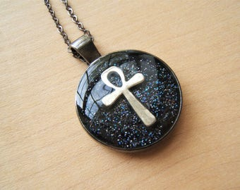 Silver Ankh necklace. key of life. Ancient Egyptian jewellery. Gunmetal. Black night sky background.