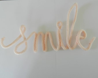 """Wire and pink knitting """"smile"""" Word"""