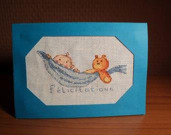 Boy embroidered cross stitch birth congratulations card: baby in hammock