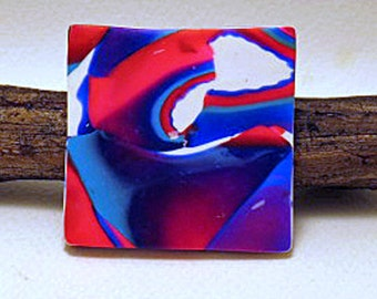Brooch. Small square brooch in the New Interstellar design. Bright reds and blues patterns over white ground brooch.