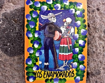 Traditional Mexican painting on metal ex voto style skeletons in love serenading to his sweetheart