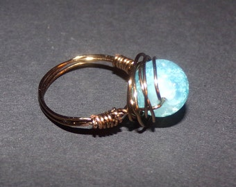 Copper colored wire wrap ring with a light blue glass ball