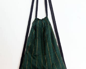 Mens drawstring rucksack, stripey Laos silk fabric, with navy nautical cord handles and brown leather details. Green rucksack. Ready to ship