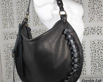 Borsa in pelle e cuoio in color nero, si può indossare a monospalla o a tracolla che è staccabile grazie a dei moschettoni. Collezione Worm.