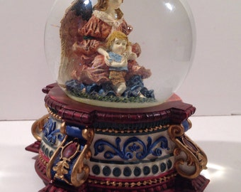 "Musical Snow Globe on an Ornate Base with a Guardian Angel holding a Child in Her Lap and playing ""Joy to the World"" from Crafts by the Sea"