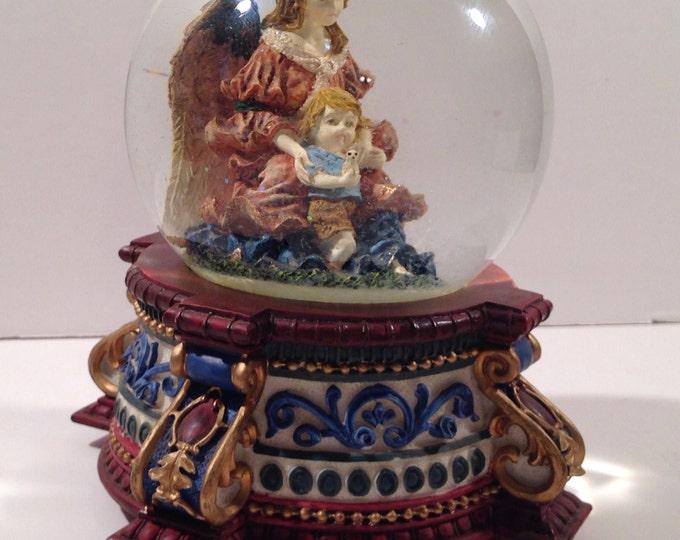 """Musical Snow Globe on an Ornate Base with a Guardian Angel holding a Child in Her Lap and playing """"Joy to the World"""" from Crafts by the Sea"""