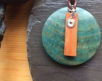 Teal colored wooden pendant with Yew and silver spiral charm