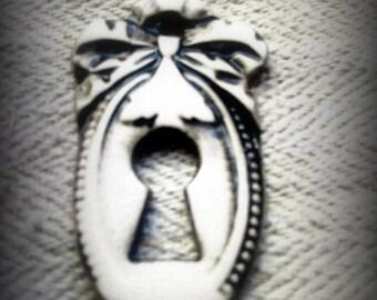 Plaque émaillée de forme médaillon trou de serrure : Petit noeud