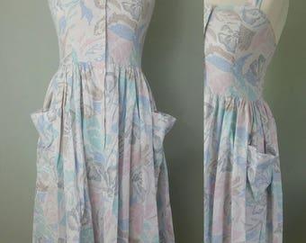 "1980s Vintage Retro Summer Dress. Halter Neck. White Pastel  Flower Print. Flared Skirt. Pockets. Mid Length. Bust 34"" Size 8-10"