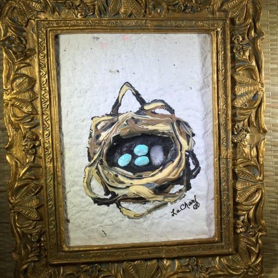 Gold framed turquoise bird eggs in a nest