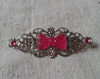 small brooch and pink rhinestone bow