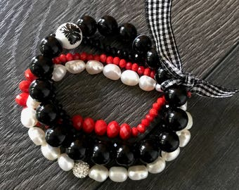 white pearls with black and red stones stretching bracelet with ribbon