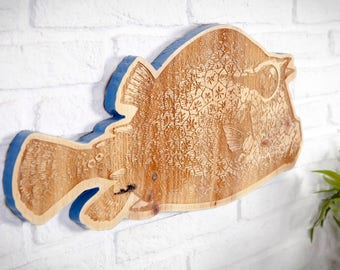 Recycled wood poster with fish engraving.