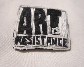 """broche brodée de perles et de fil """"art is resistance"""", noir et blanche."""