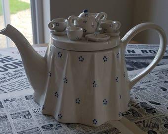 Teapot with tea set on lid