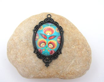 A black pendant with glass cabochon flower on turquoise background