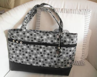 black and white fabric and black faux leather bag