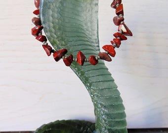 Red bracelet dark gemstones and seed beads.