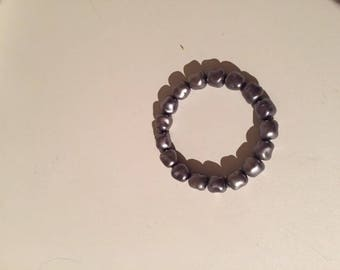 Bracelet has grey pearls