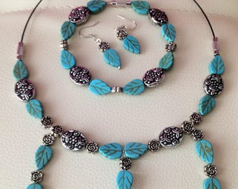 A set of jewelry from turquoise. Ornaments from natural stones. Necklace, turquoise earrings with antique beads and charms. Bijouterie.