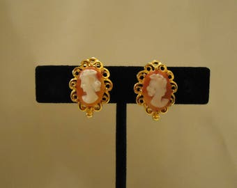 Oval Shaped Cameo Clip On Earrings Gold Metal Edges Scrolls Orange Peach Colored Background White Cameo Face Profile Vintage 1970's Jewelry