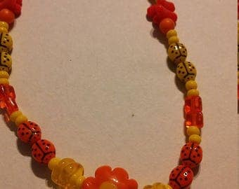 Orange glass bead and lady bug