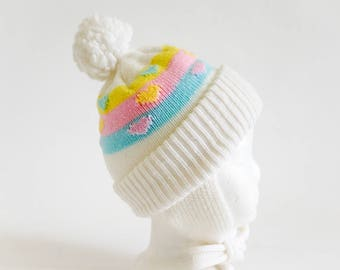 Vintage 1980s Baby Size 3-6M Knit Cap, White Acrylic Pastel Color Bands with Hearts Pom Pom Tassle Ear Flaps