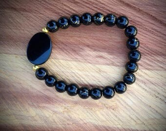 Black glass bead bracelet with gold accents