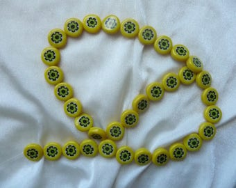 Bead, millefiori glass, 12mm Flat Yellow Coin with flower design. Sold per 16 inch strand. There are 35 beads on the strand.