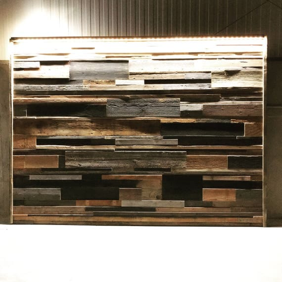 Accent wall reclaimed wood scrap art staggered, uneven patched. Dimmable color changing lighting