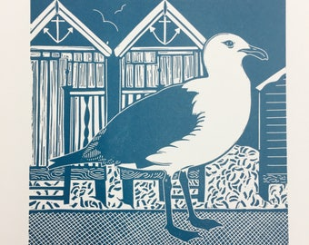 Linocut print of Seagull with beach huts