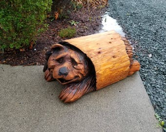 Chainsaw carving of bear in log