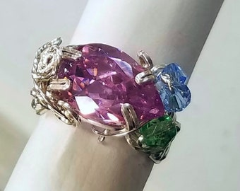 A pink pear cut CZ accented with light blue and green crystals is perfect for summer styles.  Feminine and fancy, sure to please.  Size 7