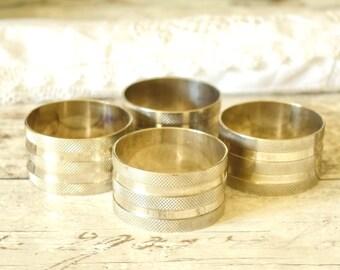 Set napkin rings, four vintage, embossed silver tone metal