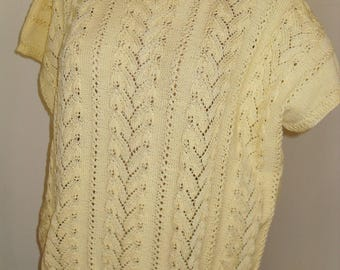 Knit yellow ladies sweater of soft yarn, with braids, freely falling.