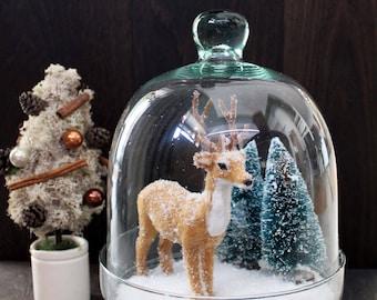 Glass bell with deer, snow, fir trees
